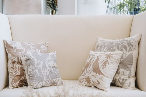 alexa topote's neutral colored pillow creations for her company, by hand mexico, boast otomi embroidery