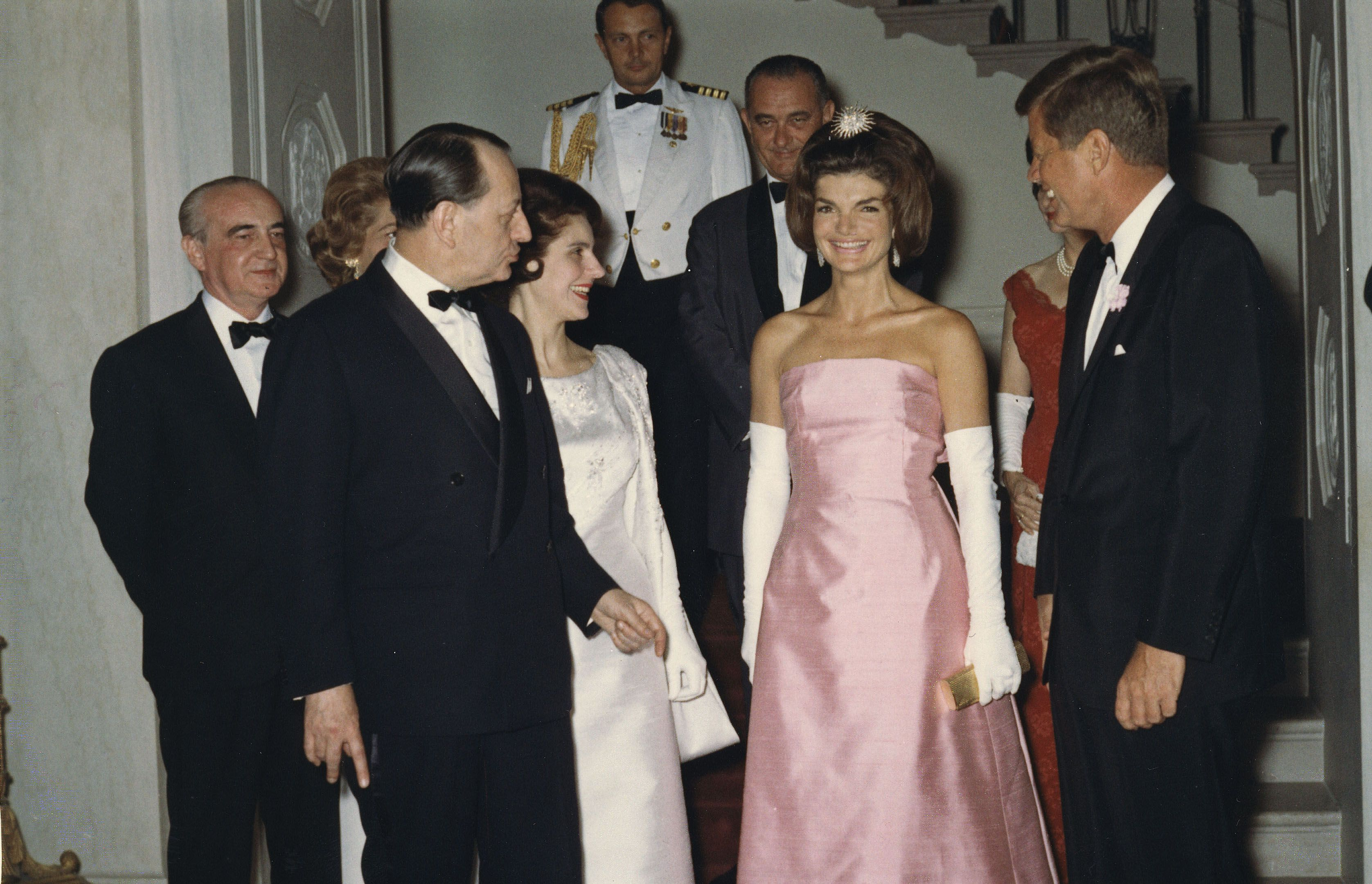 Jackie stuns in a pale pink strapless gown as she and the President greet guests for an official dinner at the White House.