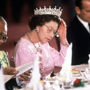 peking, china   october 13  the queen adjusting her tiara whilst reading the menu before dinner is served at a banquet held in her honour during her visit with prince philip to peking, china the queen is wearing queen mary's 'girl's of great britain and ireland' tiara  photo by tim graham photo library via getty images