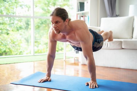 The sport man 's doing push ups on the floor at home.