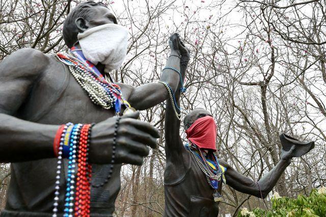 una estatua que honra al maratón de boston con sus dos figuras de corredores con mascarilla y medallas tras la suspensión de la prueba