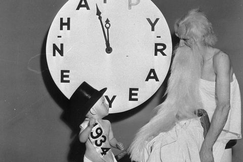 baby new year with father time by clock