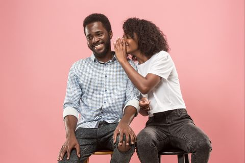 The young woman whispering a secret behind her hand to afro man