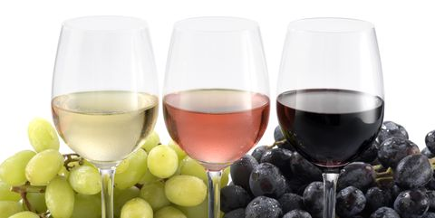 There wine glasses with fresh white and black grapes