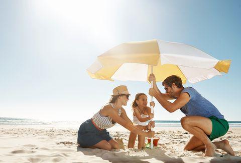 unos padres con una niña colocan una sombrilla en la arena de la playa
