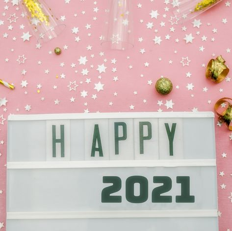 a pink background with confetti and streamers with a sign that says happy 2021