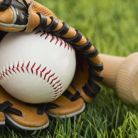ball inside catchers mitt and bat on grass