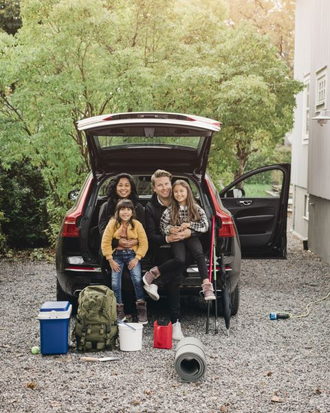 smiling parents sitting with daughters in trunk of electric car