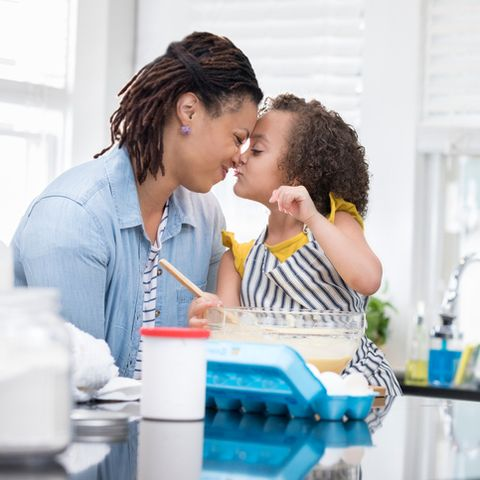 loving mom gives young daughter eskimo kisses as they bake a cake together