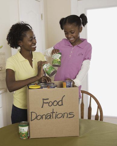 mother and daughter putting canned food in donations box indoors