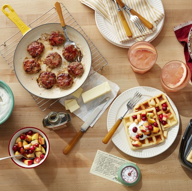 a table with sausage and waffles and grapefruit drinks