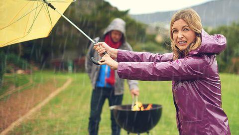 vrouw barbecuet in de regen met paraplu erboven