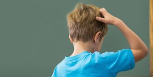 Thinking pupil scratching his head in classroom