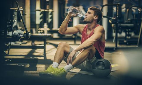 Thirsty athletic man drinking water on a break in a gym.