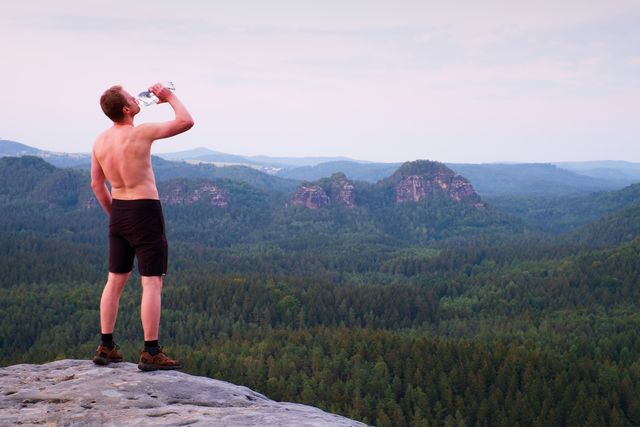 thirsty hiker in pants with bottle of water sweaty tourist
