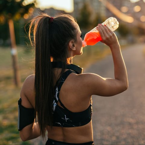 Thirsty woman with headphones drinking sports drink from her bottle