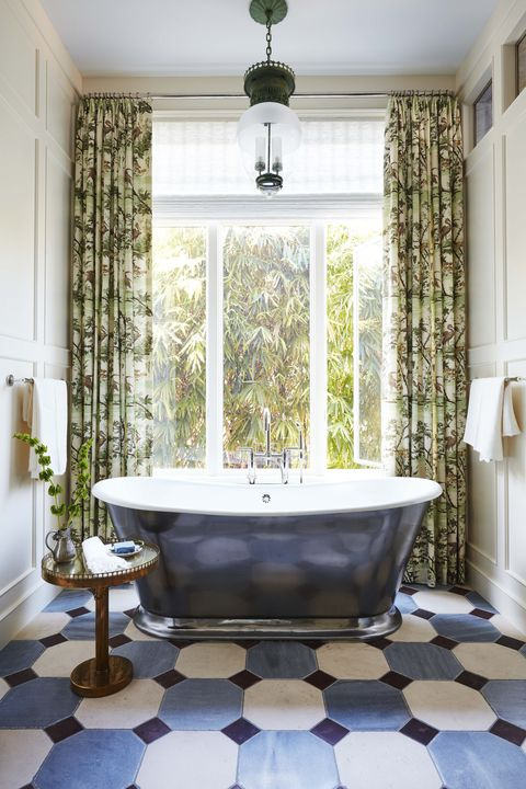 graphic flooring tile in the primary bath with a burnished cast iron tub in front of a window