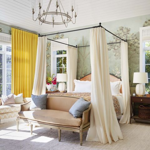 linen panels drape an iron and walnut bed and there are yellow curtains on the windows