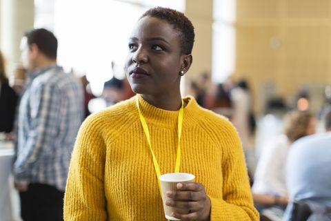 Thoughtful businesswoman drinking coffee at conference