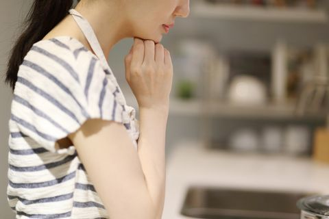 thoughtful housewife with hand on chin