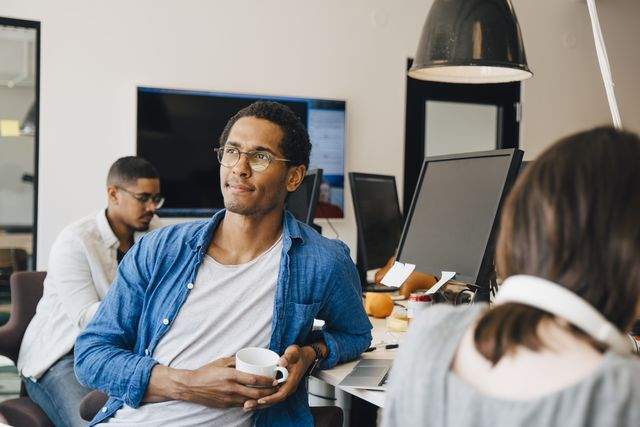 thoughtful male computer programmer looking away while sitting by colleagues at desk in office