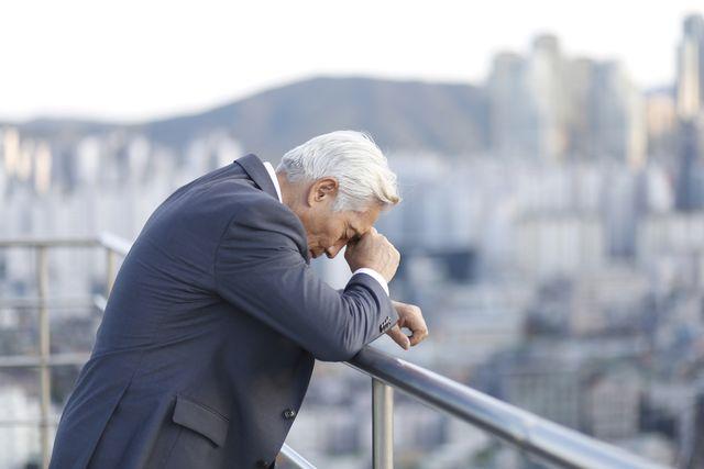 thoughtful senior businessman leaning on balcony railing