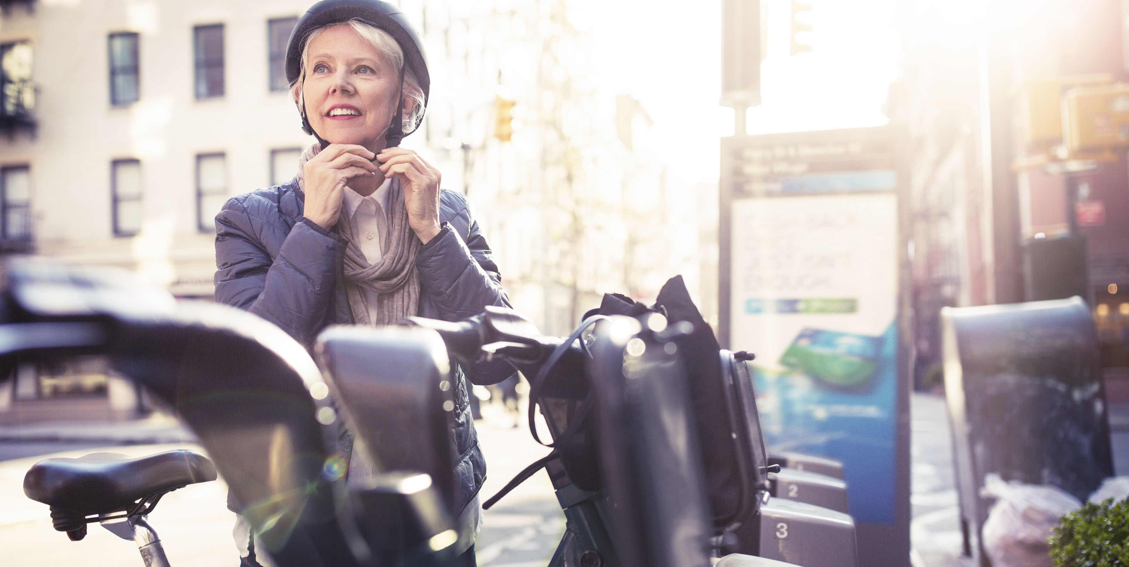 Thoughtful senior woman wearing helmet while standing by bicycles