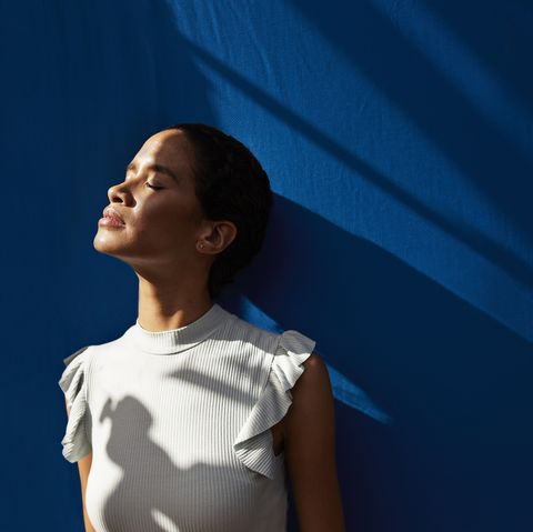 thoughtful woman standing against blue wall