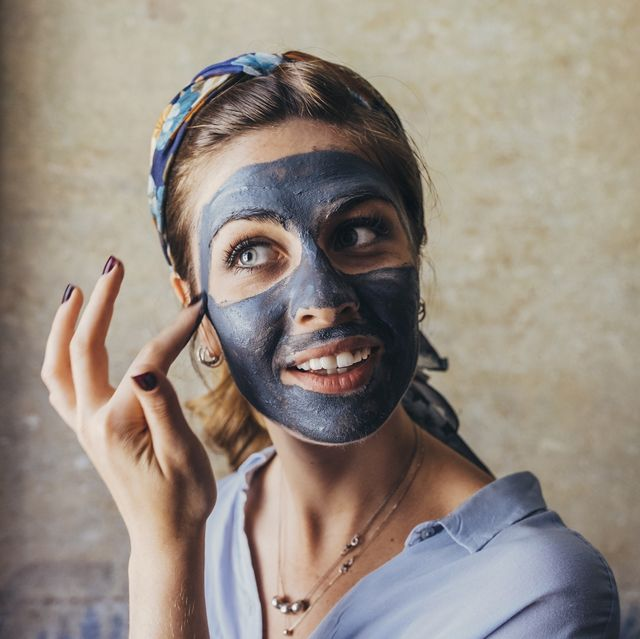 Thoughtful young woman smiling while applying facial mask against wall at home