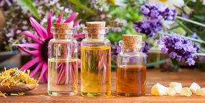 Three bottles of essential oil with frankincense, lavender, echinacea, chamomile and other herbs