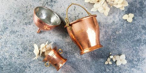 set of 3 copper miniatures on concrete background with white flowers