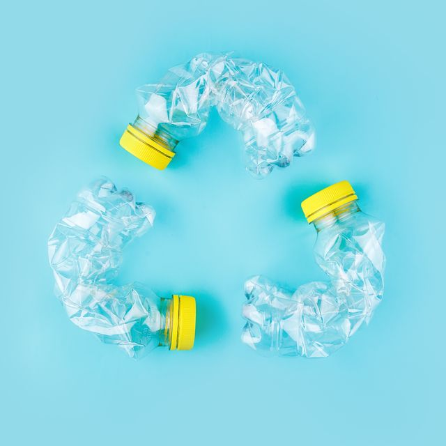 three crashed plastic bottles in recycle logo