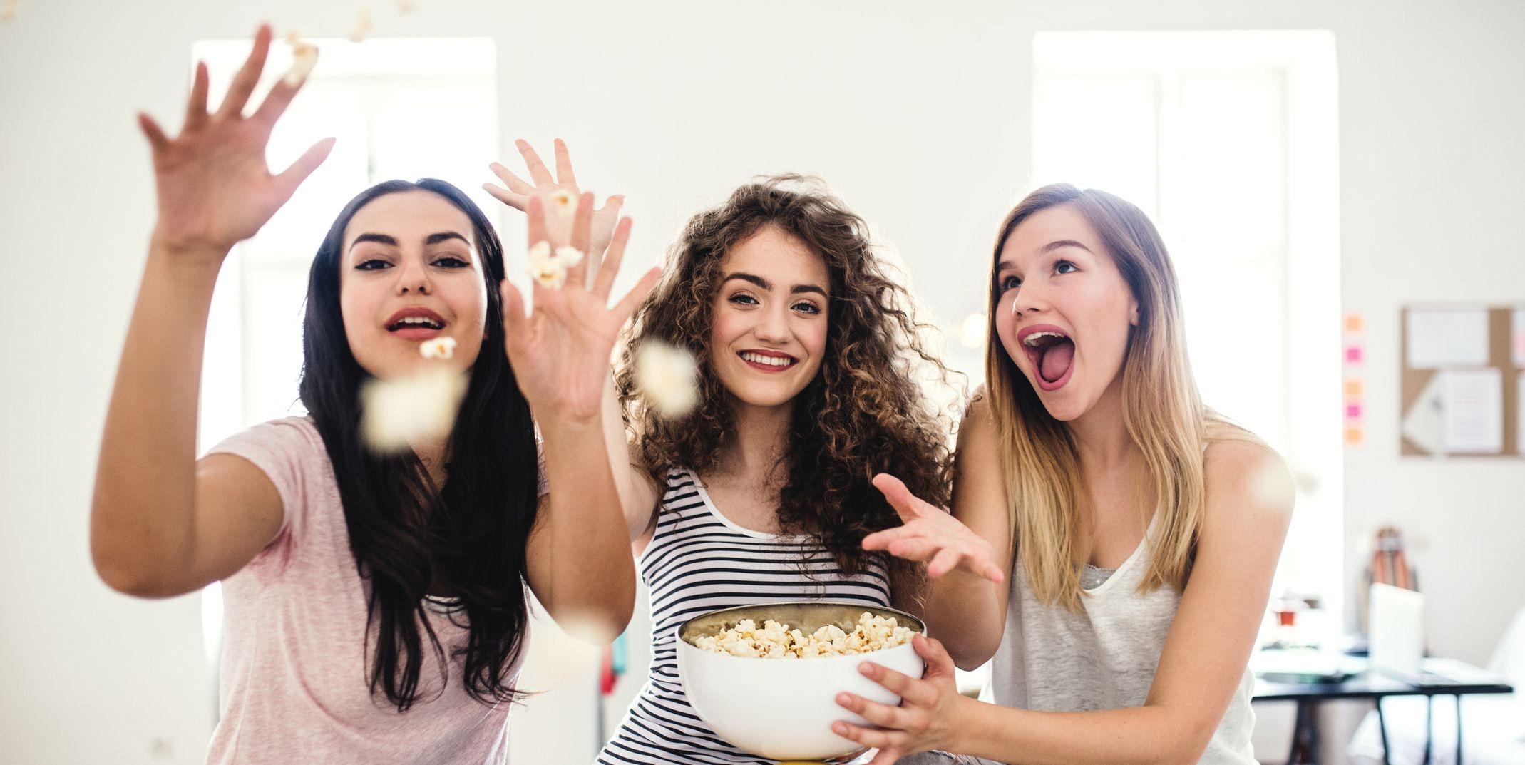 Three female teenager friends eating popcorn at home, having fun.