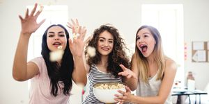 Three female teenager friends eating popcorn at home, having fun.