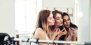 Three female teenager friends putting on lipstick in front of the mirror at home.