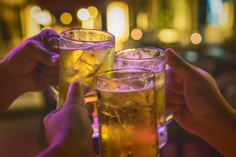 Three Glasses of Beer cheers together between friend in the low light bar and restaurant. relax and drink concept