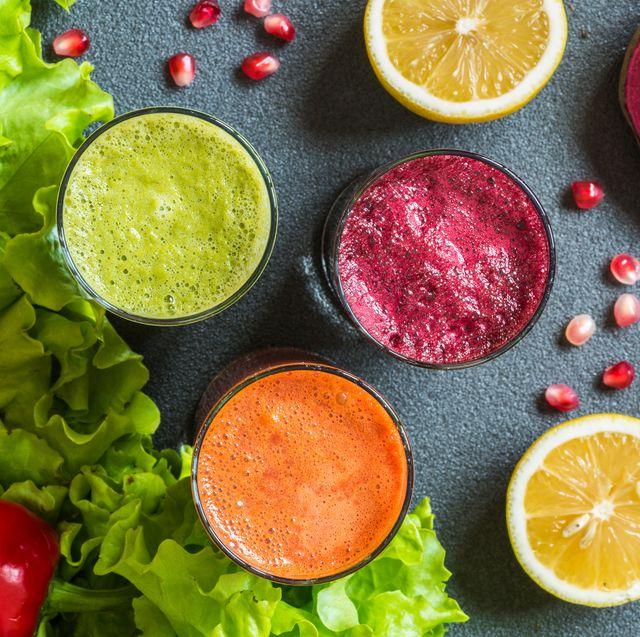 three glasses of different fresh juice beet, carrot and kiwi juices on grey background