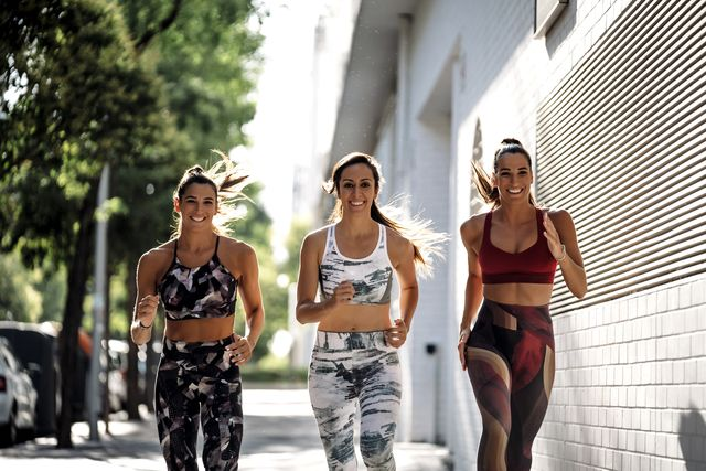 three happy sporty young women running in the city