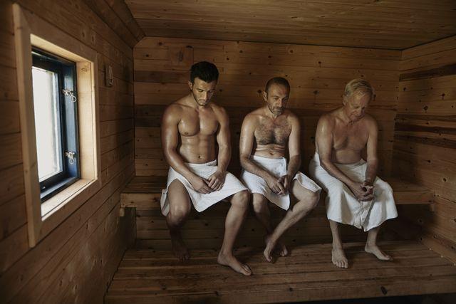 tres hombres sentados en una sauna con una toalla blanca y desnudos de cintura para arriba