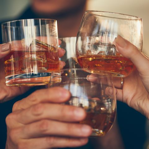 Three people makes a toast with whiskey