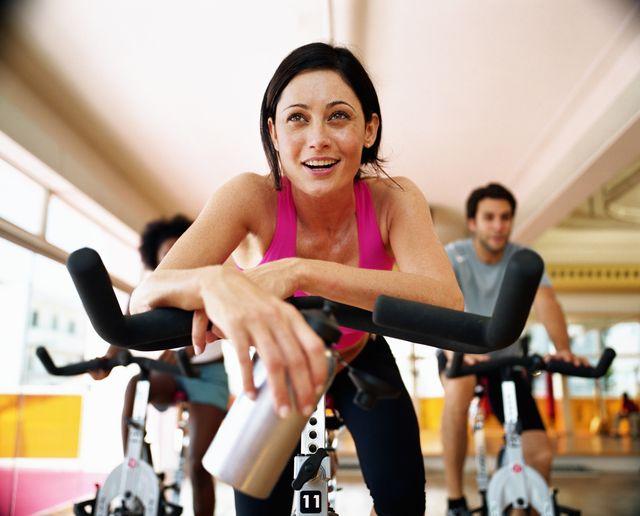 tre persone si allenano sulla cyclette
