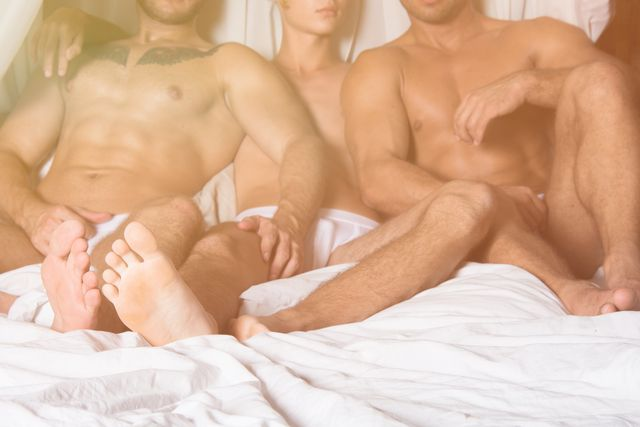 three men resting in bed together