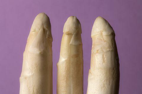 Three stalks of white asparagus suggestive of three penises