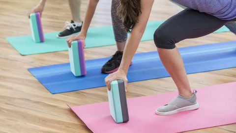 three women use exercise blocks for lunges at the gym