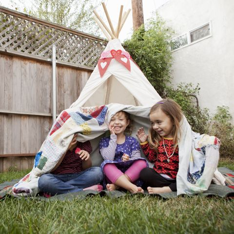 three young girls in garden hiding under blanket