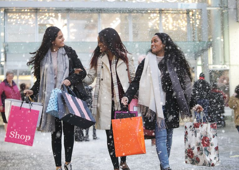 three-young-women-in-town-shopping-in-th