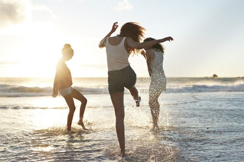 three young women kicking water and laughing on the beach