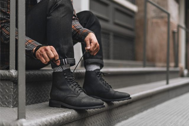man lacing up thursday boot co boot