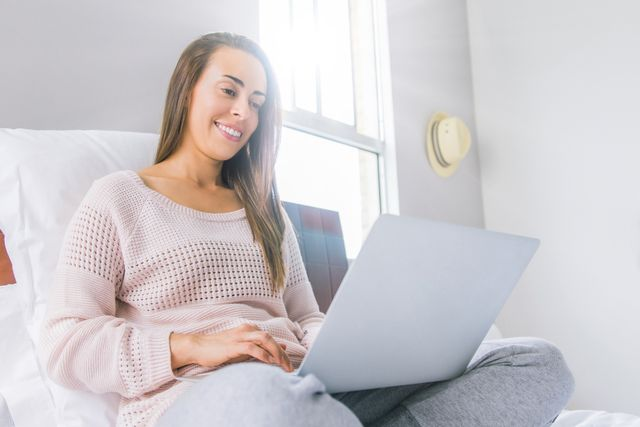 happy latin american woman working at home in bed using her laptop computer during the covid 19 quarantine   new lifestyle concepts