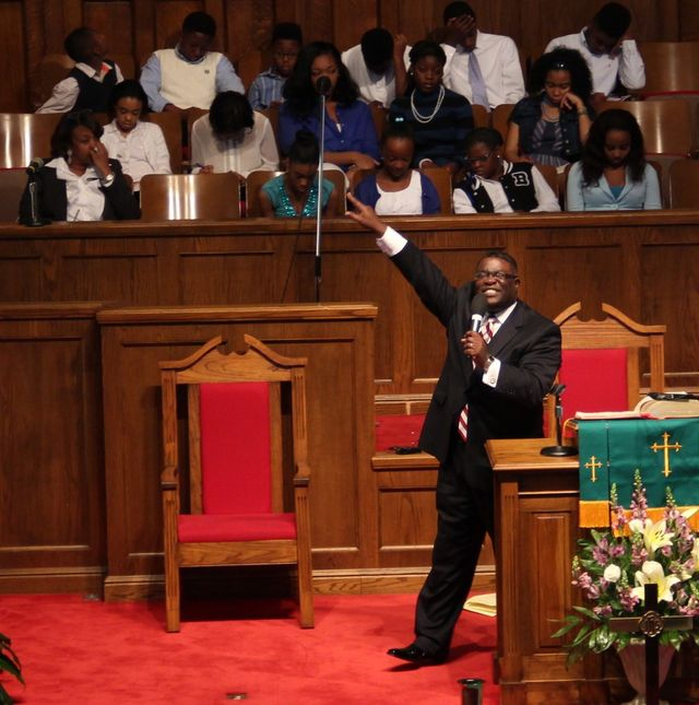 reverend arthur price jr preaching at church while the choir looks on
